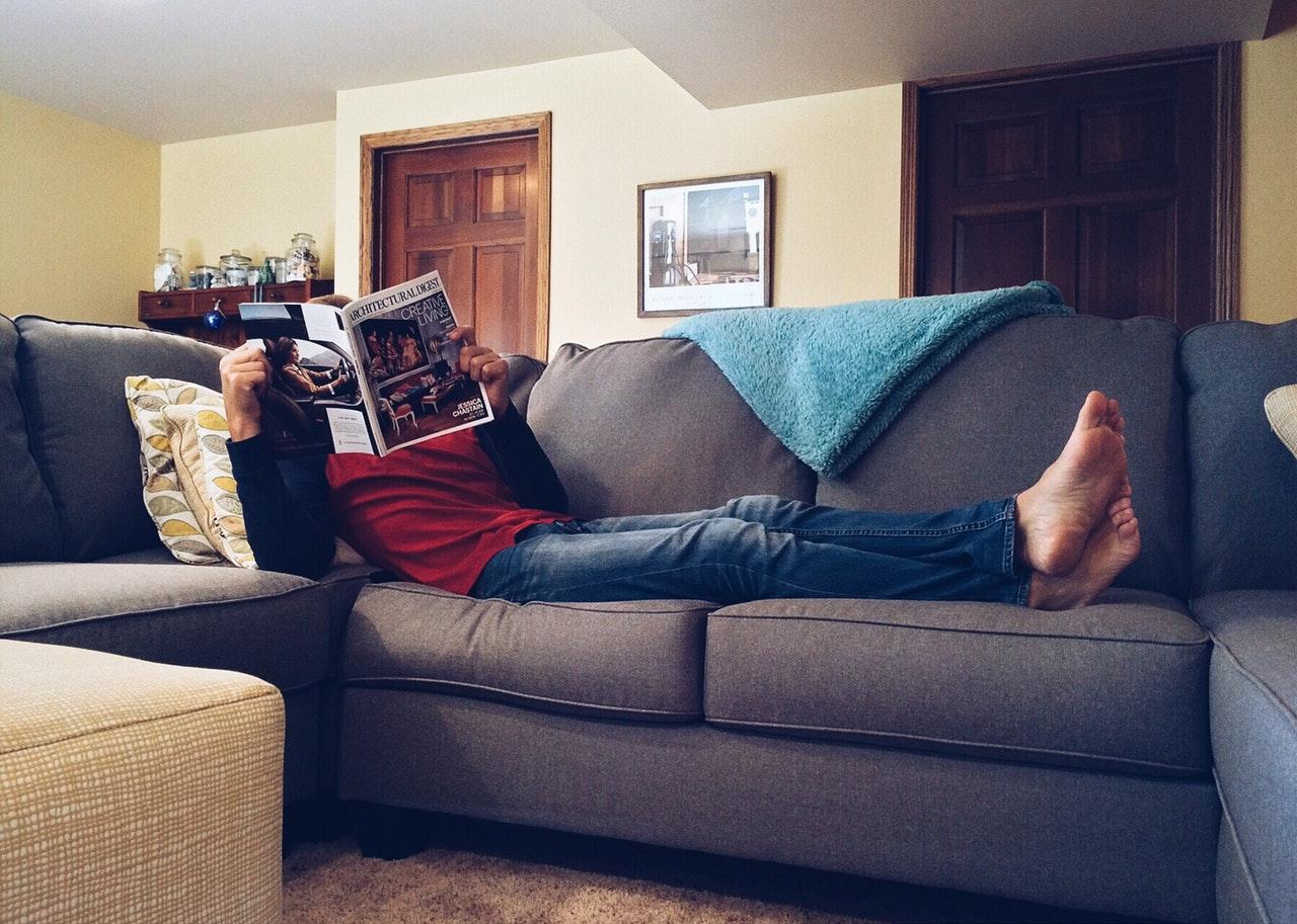 Person ligger i sofa med tæppe
